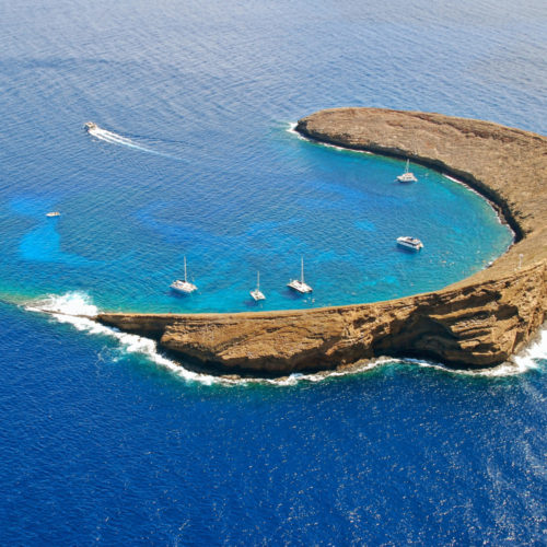 An aerial view of Molokini Island Hawaii, with boats moored inside