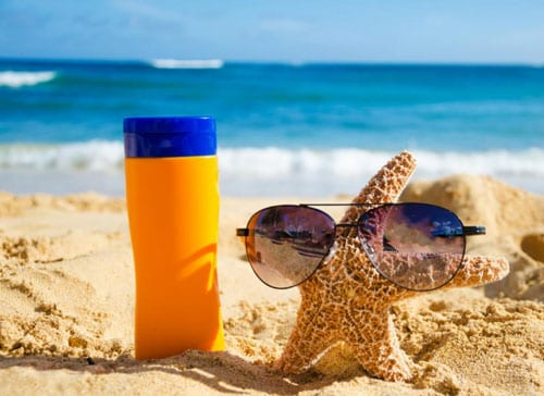 A Bottle Of Reef Safe Sunscreen And Starfish On The Beach